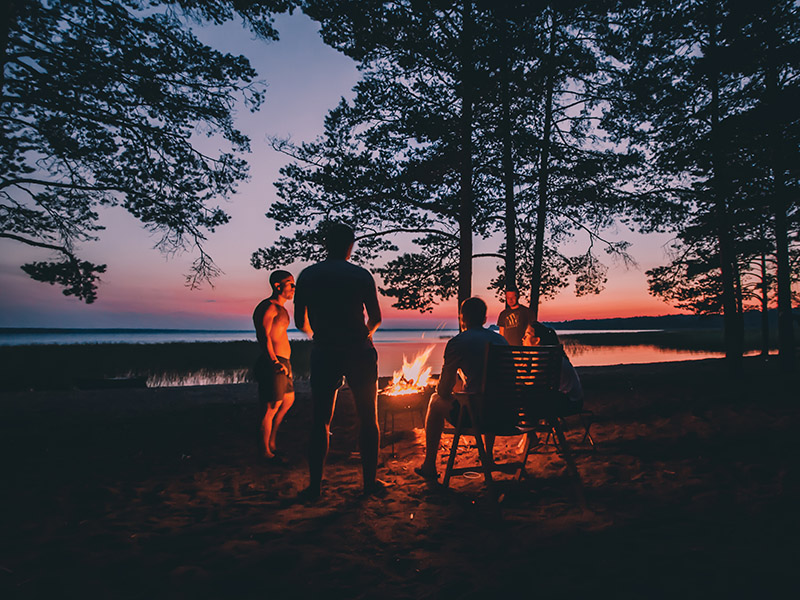 Group Of Young Happy Friends Sitting By The Fire At Summer Beach, Grilling Sausages And Drinking Beer, Talking And Having Fun